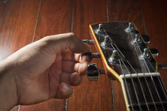 Hand turning acoustic guitar. Royalty Free Stock Photography