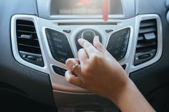Hand turning on car radio system. Button on dashboard in car panel stock image