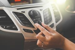 Hand turning on car radio system. Button on dashboard in car panel royalty free stock images