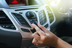 Hand turning on car radio system. Button on dashboard in car panel stock photos