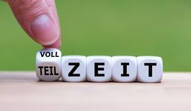 Hand is turning a dice and changes the German word `VOLLZEIT` to `TEILZEIT`. stock photos