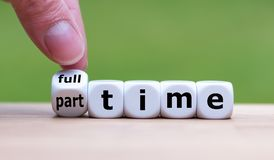 Hand is turning a dice and changes the word `full-time` to `part-time` royalty free stock image