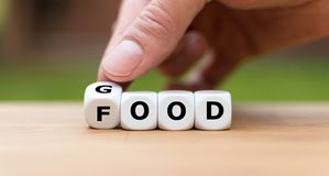 Hand is turning a dice. And changes the word `good` to `food stock images