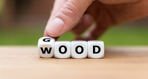 Hand is turning a dice. And changes the word `good` to `wood royalty free stock images
