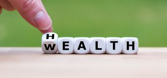 Hand is turning a dice. And changes the word `Health` to `Wealth royalty free stock photos