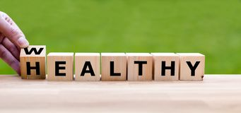 Hand is turning a dice. And changes the word `Healthy` to `Wealthy royalty free stock photo