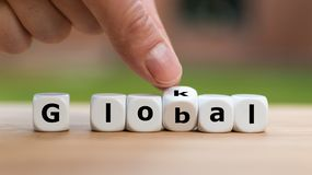 Hand is turning a dice. And changes the word lokal to global stock image
