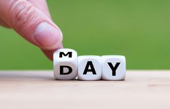 Hand is turning a dice. And changes the word `may` to `day stock images