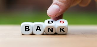 Hand is turning a dice. And changes the word `Bad` to `Bank stock images