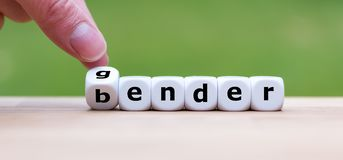 Hand is turning a dice. And changes the word gender to bender stock photos