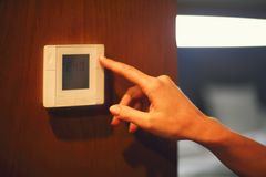 Hand turning on digital climate control royalty free stock images