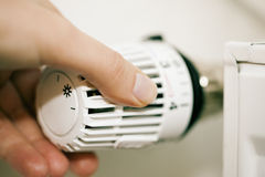 Hand turning down the thermostat Royalty Free Stock Images