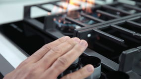Hand turning on the gas cooker in kitchen. Close up shots of kitchen activities while turning on and off fire on gas cooker cooktop stock video