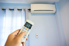 Hand turning on home air conditioning Royalty Free Stock Image