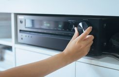 Hand turning on Home-theater amplifier. System royalty free stock image