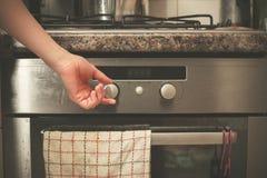 Hand turning knob on stove Royalty Free Stock Photography