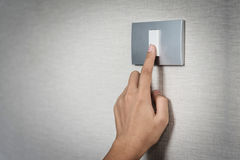 Hand turning on or off on grey light switch with textur. Close up hand turning on or off on grey light switch with texture background. Copy space stock image
