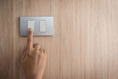 Hand turning on or off on grey light switch with wooden. Close up hand turning on or off on grey light switch with wooden background. Copy space royalty free stock photography