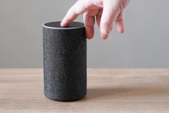 Hand turning off smart speaker microphone. Hand pushing button on smart speaker - turning or switching off microphone for privacy concerns royalty free stock image