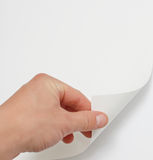 Hand turning page. Hand turning a white page royalty free stock photo