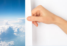 Hand turning page. Hand turning blank page with blue sky and clouds royalty free stock images