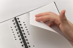 Hand turning page of blank spiral notebook Royalty Free Stock Photography