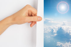 Hand turning the page revealing blue skies Royalty Free Stock Photography