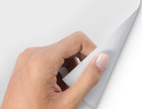 Hand turning page of white paper Stock Image