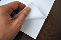 Hand turning page. Hand turning a white page write on whatever you want Royalty Free Stock Photo