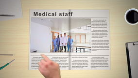 Hand turning pages of medical news magazines stock video footage