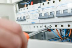 Hand turning screwdriver in fuse box. Arm royalty free stock photo