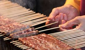 Hand while turning the skewers of cooked meat Royalty Free Stock Photos