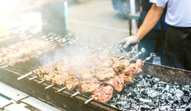 Hand turning the skewers with kebab on mangal. In smoke Stock Image