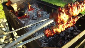 Hand turning skewers with meat on brazier outdoors stock video