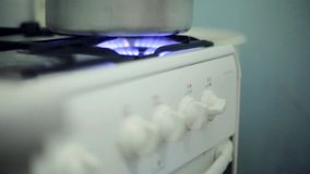 Hand turning switch off of burning gas stove with saucepan. Close up. Cooking stock footage