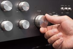 Hand turning up the volume in a stereo.  stock photo