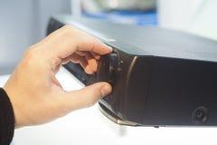 Hand turning volume knob. Up, closeup stock photography