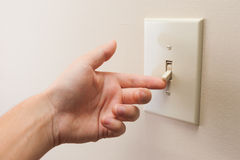 Hand turning wall light switch off. stock photos