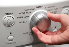 Hand turning on washing machine Stock Images