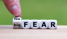 Hand turns a dice and changes the expression `big fear` to `no fear`. stock photo