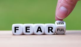 Hand turns a dice and changes the expression `fearful` to `fearless`. Hand turns a dice and changes the expression `FEARFUL` to `FEARLESS stock images