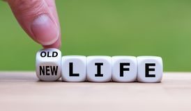 Hand turns a dice and changes the expression `old life` to `new life`. Hand turns a dice and changes the expression `old life` to `new life royalty free stock image