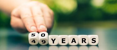 Hand turns dice and changes the expression `49 years` to `50 years`.