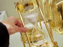 Several hourglass close up. Hand turns the hourglass on a gold stand stock images