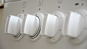 Hand turns knob on stove Royalty Free Stock Image
