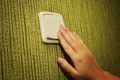 The hand turns off electricity. The girl`s hand presses the light switch Stock Image