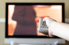 Hand with a TV remote control. Hand with a remote control on the TV background Royalty Free Stock Photos