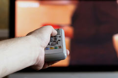 Hand with a TV remote control. Hand with a remote control on the TV background Stock Photo