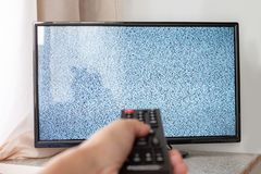 Hand with TV remote control in front of the screen with white noise on it - tuning the television channels and connecting problems.  royalty free stock photos
