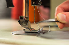 Hand with tweezers gives the thread the needle of the sewing machine. Royalty Free Stock Photo